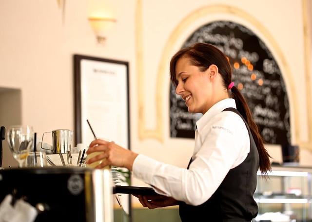 mladá číšnice obsluhující zákazníky